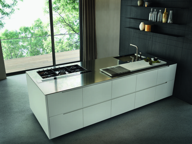 """Varenna_PHOENIX_kitchen with glacier white embossed lacquered base units, personalised steel worktop Varenna by Barazza thickness 1/4"""". Steel tall units with retractable doors. Wall panels in black elm with steel shelves thickness 1/8"""" in carbone embossed lacquered finishing."""