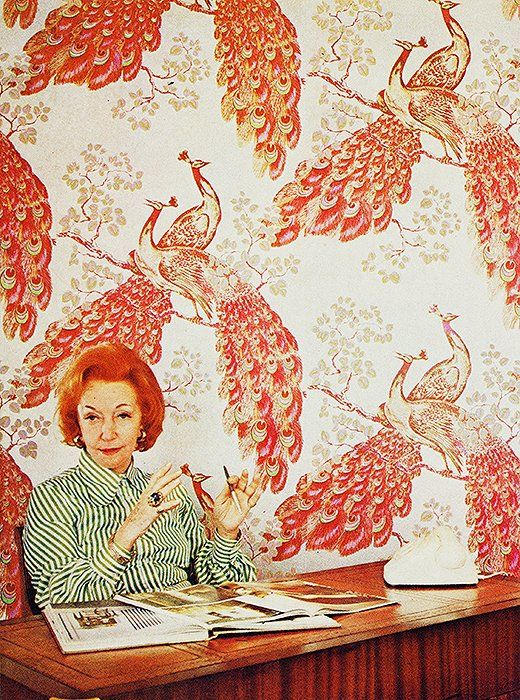 Iconic textiles designer Florence Broadhurst, whose designs were as vibrant and fascinating as her storied life, seated in front of one of her most popular patterns, Peacocks.