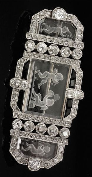 """A 1920s platinum and gold coloured metal mounted diamond, rock crystal and onyx set brooch in the manner of """"Boucheron"""", the three reverse intaglio rock crystal panels carved with putto, contained within a frame of brilliant and rose cut diamonds bordered by eight baguette cut onyx stones (total estimated diamond weight 2cts)"""