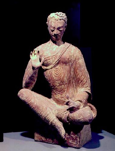 7th C. or earlier. Buddha, from a niche in the Fondukistan monastary. A Lithe and sensuous figure in an almost translucent robe draping in circular folds, a small delicate head with downcast eyes, curly hair (possibly a mustache). Dated based on Arabo-Sassanian style coins found at the site. Afghanistan. Guimet