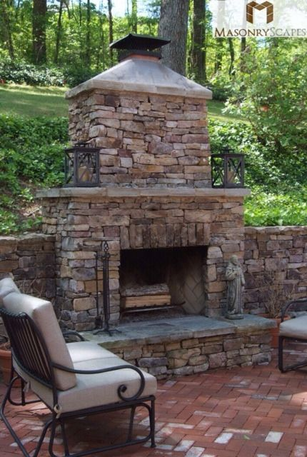 Brick paver patio with a custom-built natural stone fireplace and a moss rock retaining wall.