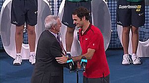 Roger Federer of Switzerland holds the Roy Emerson trophy from Roy Emerson after winning his 1000 match after the Mens final match against Milos Raonic of Canada during day eight of the 2015 Brisbane International at Pat Rafter Arena on January 11, 2015 in Brisbane, Australia.