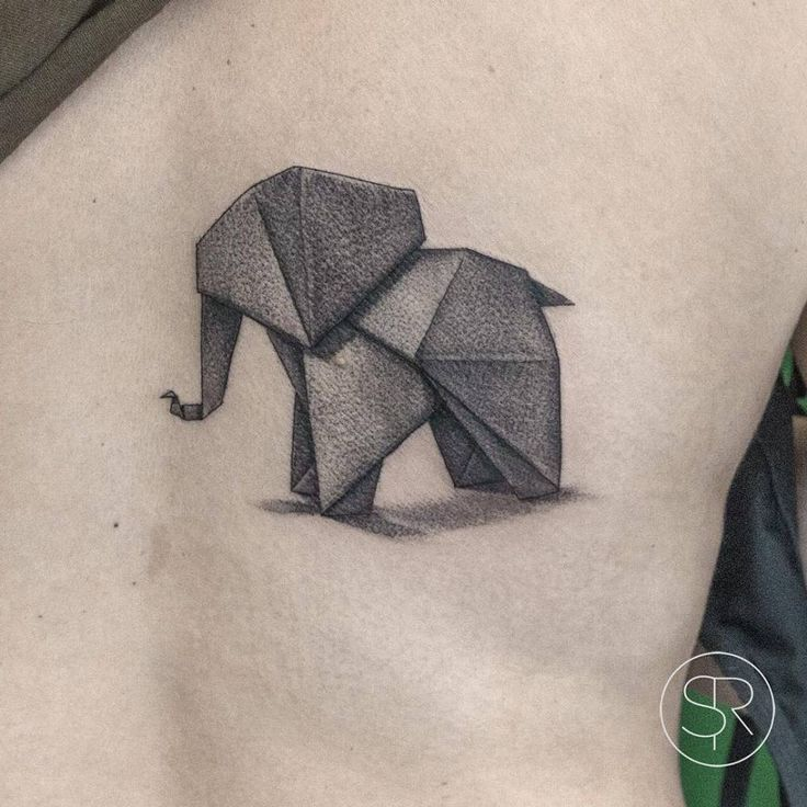 Fine line origami elephant tattoo on the right side of the back.