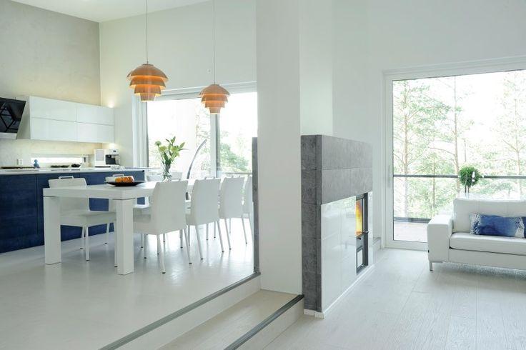 Kevään 2016 keittiötrendeihin kuuluvat jälleen värit! Valkoista keittiötä raikastavat siniseksi sävytetyt tammiviiluovet. Keittiön ja olohuoneen tilanjakajana on NunnaUunin tyylikäs mittatilaustakka.