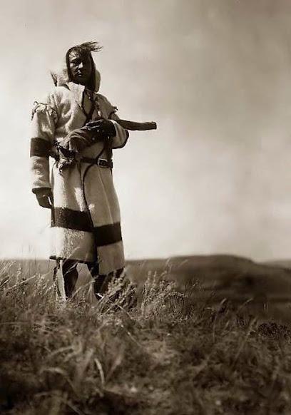 Blackfeet (Pikuni) man wearing a Hudson's Bay Blanket Capote - 1910