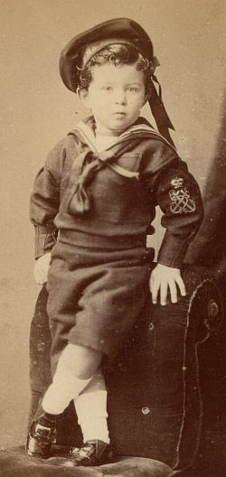 This young boy wears a traditional sailor suit with cap and collar. The fabric of his suit is probably a woolen material in dark blue. He wears white socks and low leather shoes. 1877.
