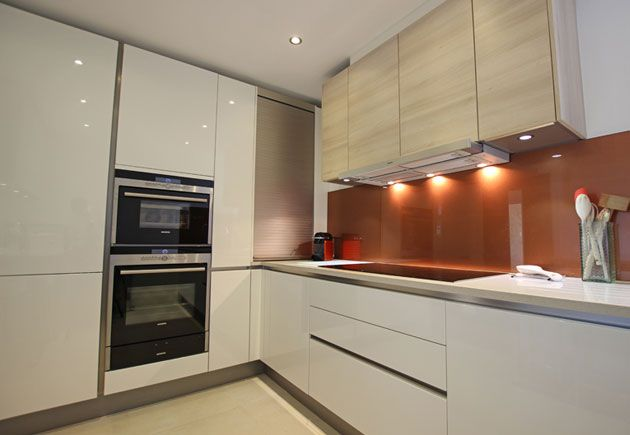 This small L shaped kitchen design is contemporary and inviting, yet also very practical. The design contains many storage solutions including a pull out larder, corner Le Mans units, and a tambour unit that was manufactured in a reduced height from the standard size in order to fit the space. The handleless design takes up less space than a handled kitchen, as do integrated appliances. #Lshapelayout #Lshapekitchen #kitchen