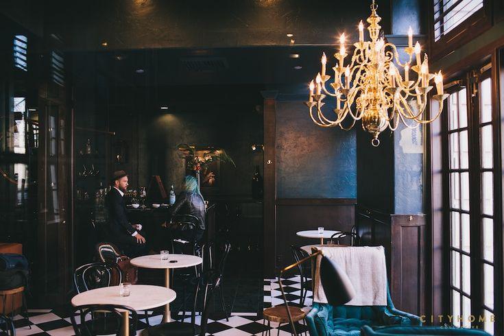 moody interiors, restaurant design, vintage chandelier, black and white tile floor, black thonet cafe chairs, blue velvet arm chairs