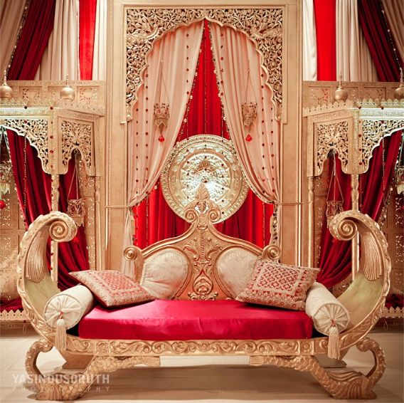 An Arabic wedding has a wedding stage and this red and gold couch for the bride and groom is incredible