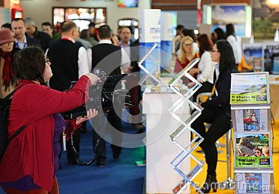 Lady cameraman filming at tourism fair in Bucharest, Romania.