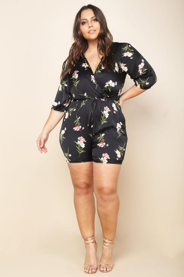 A plus size romper with a wrapped V-neckline and half sleeves. Features a belted waistline and a back keyhole. Floral print all over.