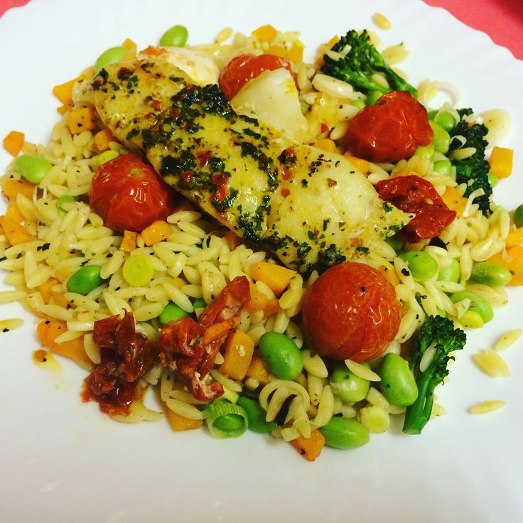 Hake fillet with garlic basil pesto on Orzo, tomatoes, edamame, squash and broccoli