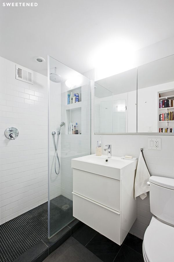 Clinton Hill Bathroom features simple IKEA vanity with deep storage drawers, a recessed medicine cabinet, and a glass-walled shower to create more space.