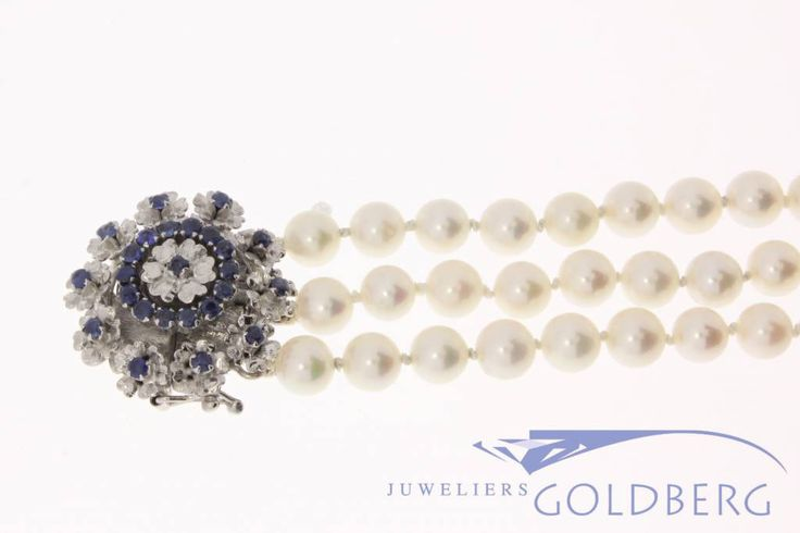 Very beautiful 3-row cultivated pearl bracelet with a vintage 18k white gold lock, set with various blue sapphires. The heavy 18k white gold lock is 26mm wide. And the pearls are between 6 and 6.5mm in diameter. For more information visit our site: http://www.goldbergjuweliers.nl/en/vintage-3-row-pearl-bracelet-white-gold-sapphire.html