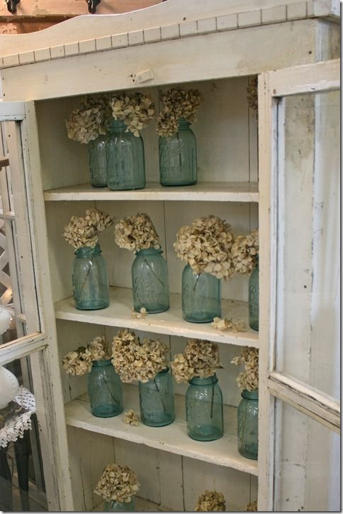 Love the aqua mason jars with the dried hydrangea blossoms.  If I do it at the cabin, my little feline friends wouldn't get at them either.