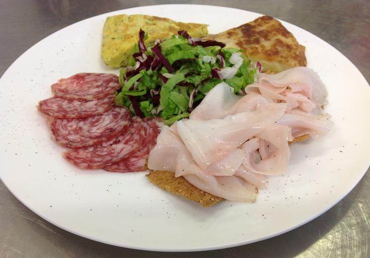 Degustazione di prodotti friulani: frico, frittata alle erbe, salame e lardo.