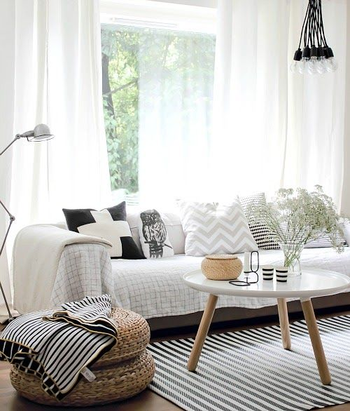 A simple, fresh Scandinavian living space. The floral blooms in white softens the black and white. Source from Penelope Home - compartiendo Inspiración
