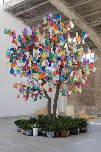 Pascale Marthine Tayou - Szukaj w Google  Wat je hier ziet is opnieuw een boom van plastic tassen. Ook hierbij zit er een boodschap achter, je kunt van recycle bare dingen ook iets moois maken. Er is dus gebruikt gemaakt van plastic e zo te zien echt hout.