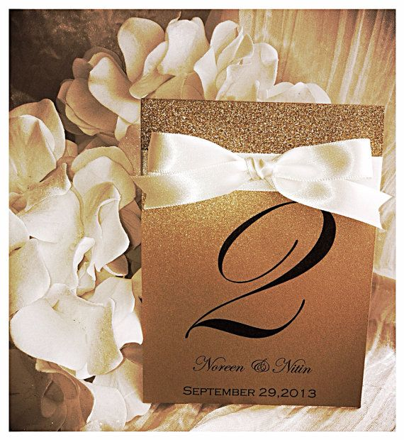 Gold shimmer glitter table number with ribbon great for weddings, sweet sixteens, birthdays, engagements parties, and other events.