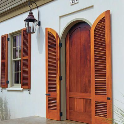 Fab Front Entrance | The beauty of stained-wood shutters is hard to beat. The natural-colored louvered panels flanking this entrance feature a curve at the top so they can be closed seamlessly into the door frame. | SouthernLiving.com