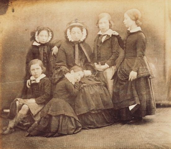 1852; Queen Victoria (1819-1901) seated with Prince Alfred (1844-1900) ; Princess Alice (1843-1878; Princess Helena (1846-1923; Albert Edward, Prince of Wales (1841-1910), later King Edward VII; and Victoria, Princess Royal (1840-1901). The Queen is seated and is wearing a bonnet and Princess Helena has her head resting on the Queen's lap.