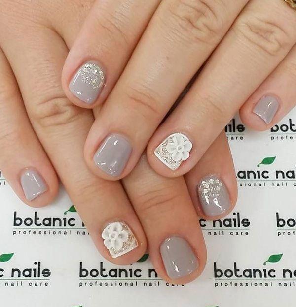 Een heerlijke op zoek grijs en wit nail art design voor de korte nagels.  Schik de versieringen in een kant ontwerp in de buurt van de nagelriem en voeg witte bloem versieringen evenals op de top voor effect.