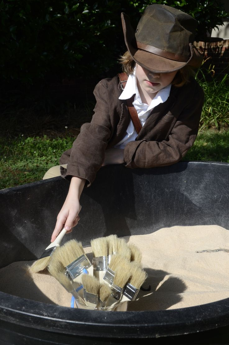 Indiana Jones: Party Activity. Sand filled tub with real gems, shells, rocks, coins  etc. for the children to uncover. I provided small shear organza bags for them to put their finds in.