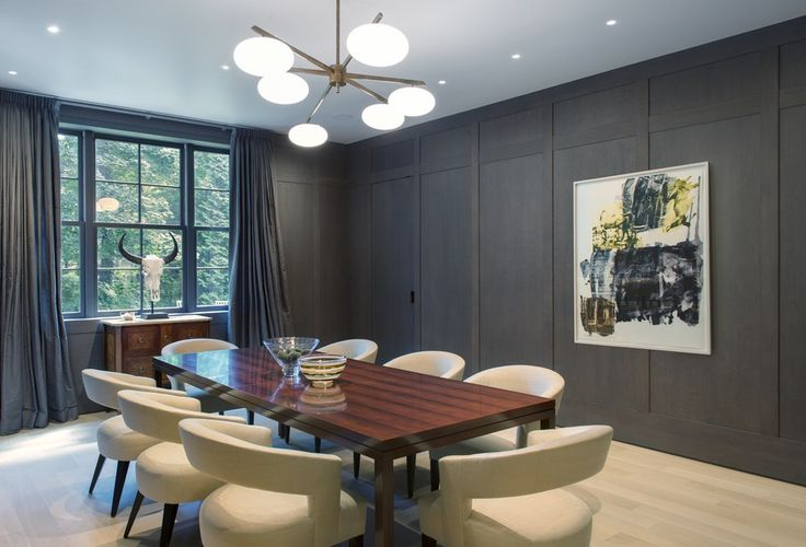 The dining room's gray-stained white-oak wall paneling conceals storage for china and glassware and displays a piece by Robert Rauschenberg. A vintage chandelier by Angelo Lelli for Arredoluce hangs above a custom-made rosewood Parsons-style table and chairs by John Boone.