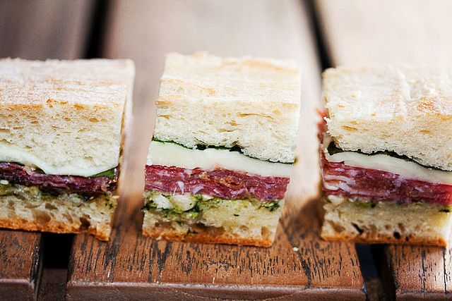 Pressed Picnic Sandwiches.  Start with a ciabatta, then add pesto, sopressata, prosciutto, cheese and basil.  Wrap tightly in plastic wrap and then press (do not sit on them, they need to go in the fridge.  lol)  Slice and serve.  Looks good.  #sandwich #food #recipes