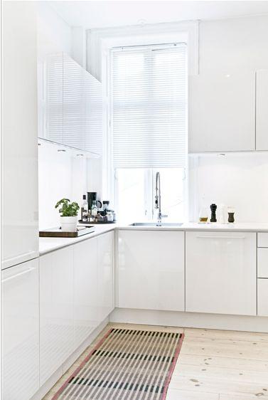 Hvidt og enkelt køkken fra HTH. Bordplade i corion. Tæppe fra Hay.