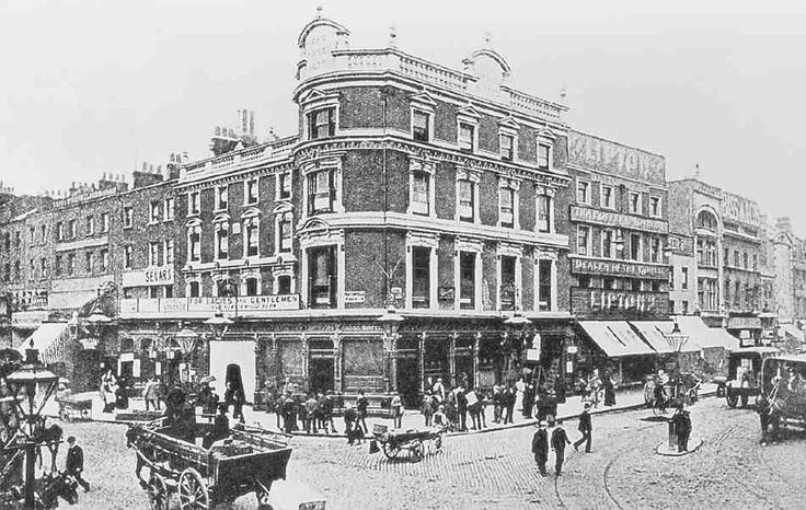 The Angel Inn, from the south-east in the late 1890s as the Angel Hotel, showing embellishments of 1869–70 and adjacent buildings along Pentonville Road (left) and Islington High Street (right)
