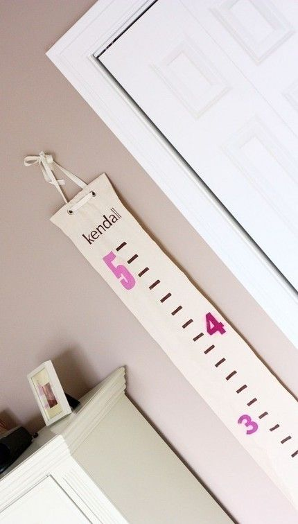 it would probably be pretty easy to make a growth chart like this with a strip of canvas, a rod, some ribbon, and fabric paint.
