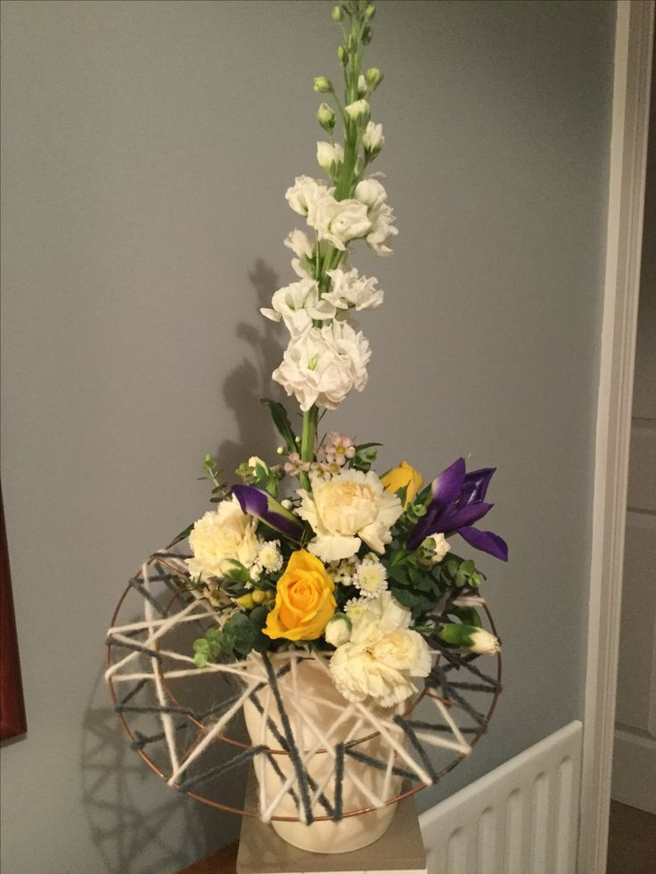 Easter arrangement with wool covered ring, stock, carnations, roses and iris.
