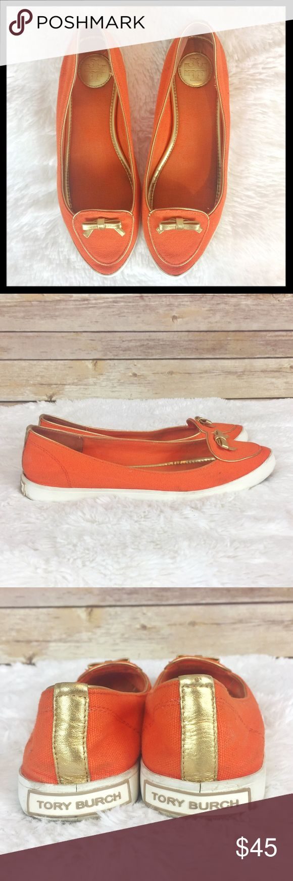tory burch // dakota canvas bow toe slip ons flats A streamlined update to the classic tennis shoe with refined looks of a loafer with the ease and comfort of your sporty favorite. A prim gold metallic leather bow and trim add some feminine polish. Made of low-key canvas, it's the definition of casual chic. Fabric upper. Orange with a gold leather bow. Logo at heel. Rubber sole. Preloved with some signs of wear as shown (faint dirt marks, wear to interior) but overall great preowned…