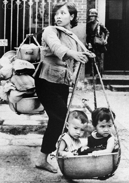 Mujer vietnamita carga en cañas de bambú a sus hijos y algunas posesiones, tratando de huir de los fieros combates en el suburbio de Cholon,  Saigón, durante la ofensiva del Tet por parte del ejército del Viet Cong, en la guerra de Vietnam. Es el mes de mayo de 1968. Foto por Wheeler/Corbis.