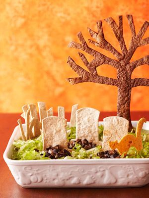 Dig In -- If You Dare Venture into this graveyard and you'll discover a tasty taco dip. Layers of refried beans, lettuce, and black olives mimic dirt and grass. Eerie shapes cut from tortilla shells complete the spooky Halloween landscape.