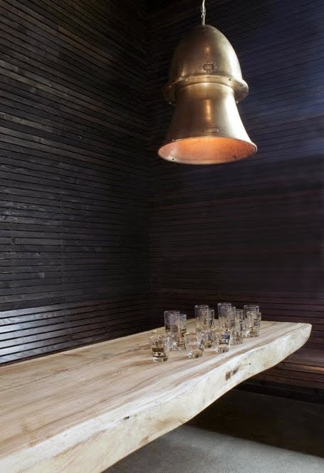 really cool dining room / bar space; love the slat panelling, one piece table and brass hanging lamp