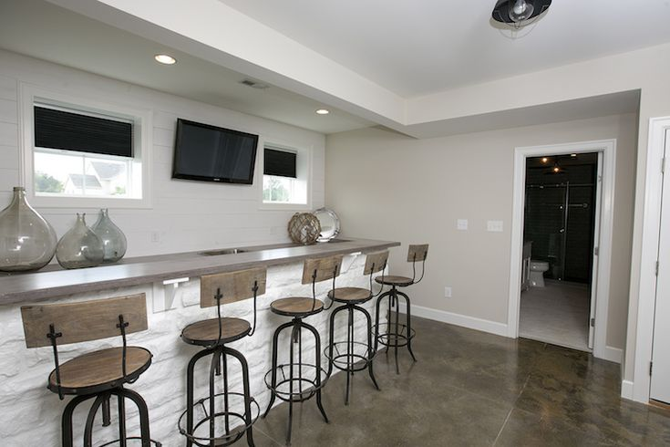 Basement features long wet bar lined with industrial barstools across from bar sink under flatscreen TV flanked by windows.