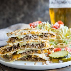 A square version of a photo with a stack of cheeseburger quesadillas on a white plate. A wedge of iceberg lettuce with tomatoes and pickles are on the side. A glass of beer is in the back.
