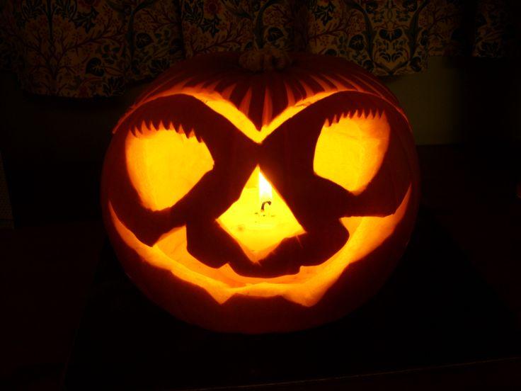 Lit Halloween pumpkin carved into a strange face