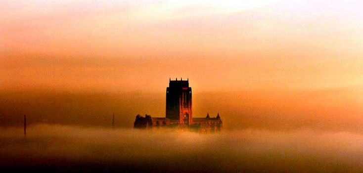 Fog covers the City of Liverpool as the Anglican Cathedral towers above it - the only visible building as the sun sets.