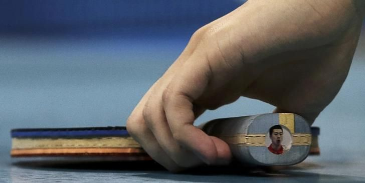 OLYMPICS-RIO-TABLETENNIS-M-SINGLES Table tennis player Ma Long of China picks up his paddle with a picture of him on the handle. REUTERS/Alkis Konstantinidis