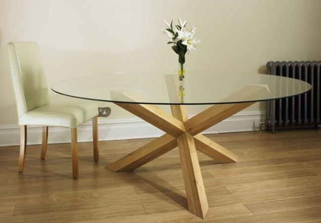 Havana Glass Round Dining Table on a solid oak pedestal Made to Order from solid European Oak this stunning table creates a statement. The cross like pedestal supports a toughened glass top leaving the pedestal open to admiration. Pictured here is the 6' version that seats up to 10.It is available in4' , 4'6 , 5' and 6' sizes and is also available untreated, otherwise the table comes waxed.Product SpecificationsGOT1 (6ft) Diameter 1830mm Height 760mm seats 8-10GOT2 (5ft) Diameter 1530mm…