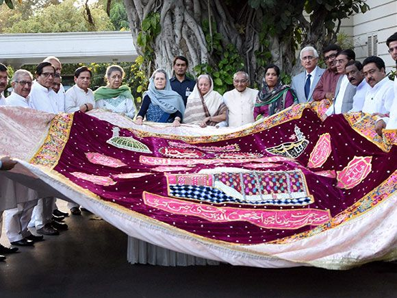 Congress President Sonia Gandhi along with others holding a 'chadar'