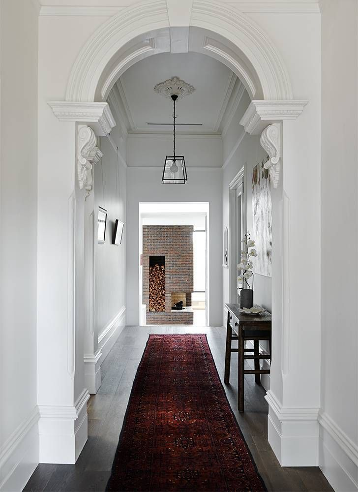 Entryway/hallway: decorative/ornate archway, extra high skirting boards, dark timber floorboards, dark red carpet runner, modern black and glass lantern pendant light, ceiling rose, wooden side table, white orchids