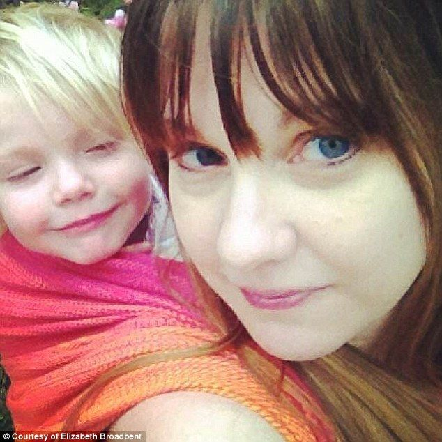 Piggyback: Elizabeth Broadbent, 34, pictured with one of her three children in a baby sling, and her partner Chris, 35, are fans of  attachment parenting