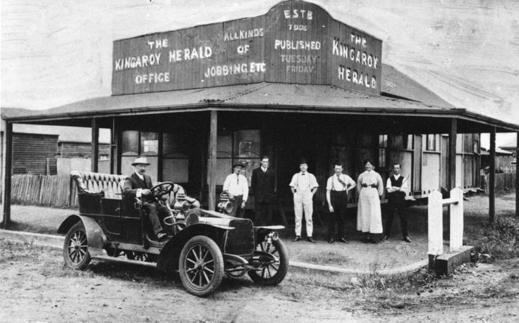 Offices of the Kingaroy Herald, Kingaroy, Queensland,  established in 1906 - Mr Archibald Blue, the Kingaroy Heralds' foundation manager is seated in his French Darracq automobile. Other staff standing from left: Charles Hill; T. Thaetcher; C. Galloway; B. Neale; Maggie Wittkop, later Mrs. W. H. Pointon and W. Lambert.