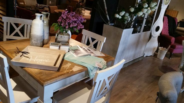 Kwadratowy stół jadalniany dla 4 osób o blacie w kolorze jasnego drewna z białymi nogami. Do kompletu białe, drewniane krzesła w stylu prowansalskim.