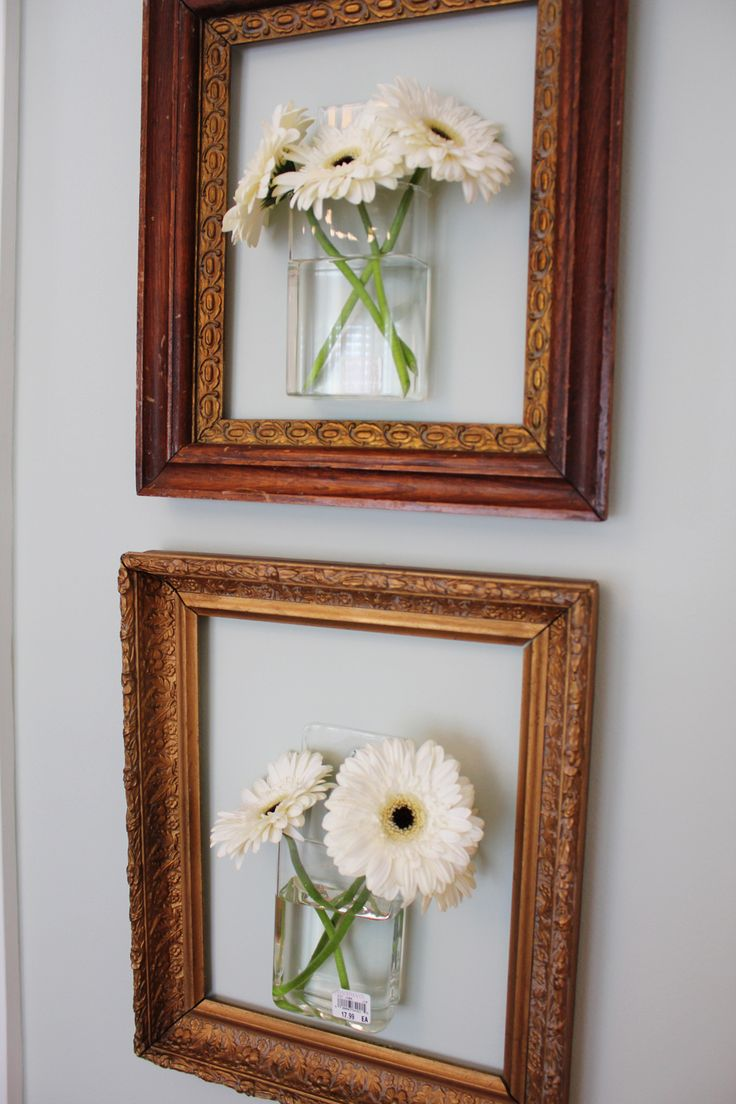 Hang mounted vases with real flowers inside empty picture frames.