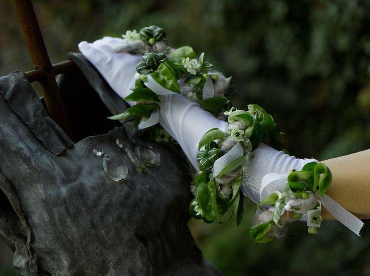 Witte handschoen met groene corsage.
